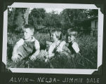 Alvin and Jimmie Dale Galbraith sit in the grass with cousin once removed, Nelda Pettigrew, Acme,...