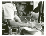 Louis Mideke forms a large bowl on his potter's wheel, Bellingham, Washington, circa 1975