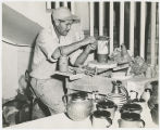 Louis Mideke working on a piece of pottery circa 1958