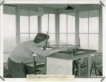 Churchill Mountain lookout tower with Patricia Langdon sighting through an alidade June 1945,...